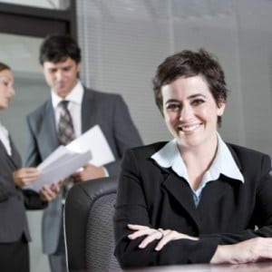 The Career Academy Diploma in Management and Team Leadership - Businesswoman smiling at desk